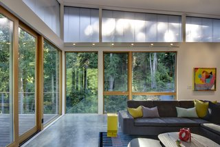 In the main house, large windows allow the forest to enter the living space, an effect opposite from its exterior presence.