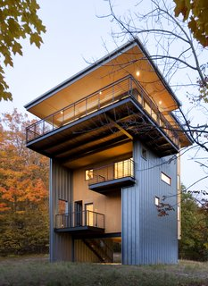 Generous balconies reach back into the surrounding forest at every level.