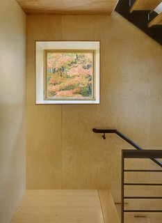 A punched-out square window acts as living art in the stairwell.