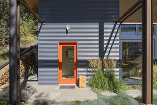 Bright orange paint trims glass doors set in the corrugated metal siding, providing a cheerful contrast.
