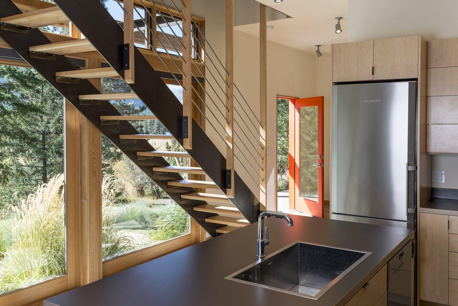Kitchen, Laminate Counter, Wood Cabinet, Refrigerator, Ceiling Lighting, Concrete Floor, and Drop In Sink An open-tread stair keeps the relatively small space from feeling cluttered or closed off from the view at the entry and kitchen.  Chechaquo by Prentiss + Balance + Wickline Architects