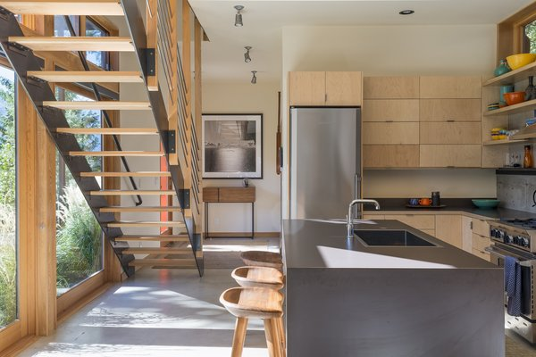 The staircase's open treads and slim, cable railing avoid blocking sight lines outside. A modest material palette, including a concrete floor, wood cabinetry, and charcoal laminate counters, cedes to the views.
