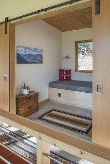 An upstairs reading nook behind sliding doors offers quiet and solitude in the open plan.