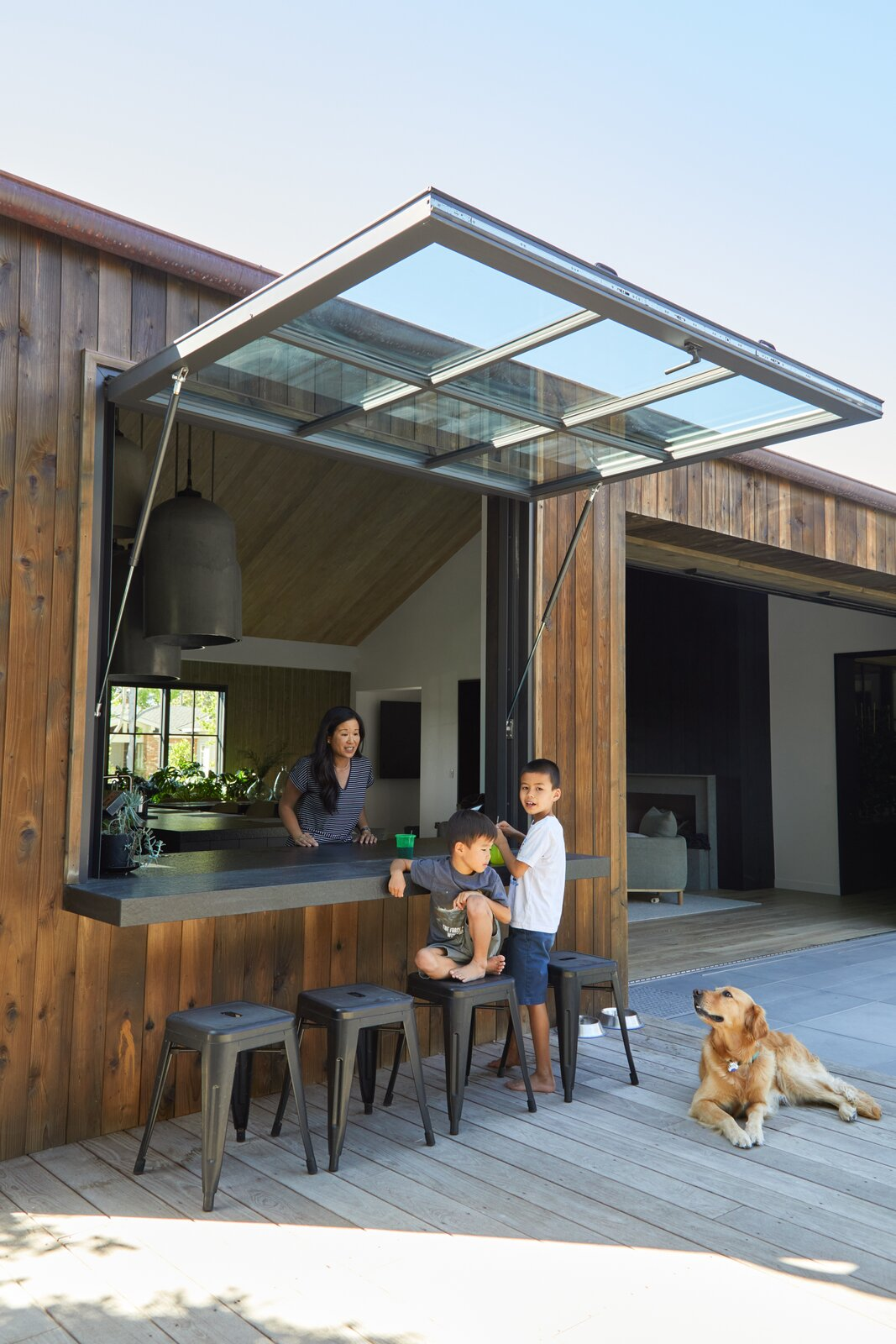 Outdoor, Back Yard, Large, and Wood The husband requested a pass-through window in the kitchen for easy entertaining.  Dwell's Favorite Outdoor Photos from A New Build for a Young Southern California Family Is All About Playful Pairings