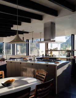 The midcentury kitchen remodel by Mutuus Studio offers views to the front, the driveway, and the back.