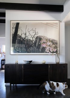 A painting by Saul hangs in the living room adjacent to the kitchen.