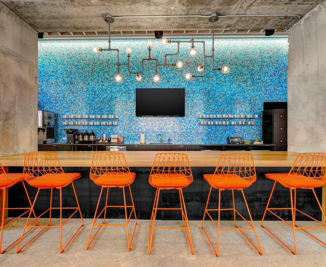 Techspace Austin's vibrant bar features a custom locally reclaimed wood bar designed by DoveTail Custom Woodworks.  Photo 9 of 11 in These 6 Collaborative Coworking Spaces Will Give you Serious Office Envy