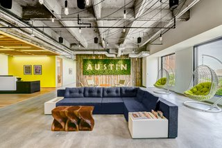 The locally-sourced reclaimed wooden wall and moss sign by Articulture bring the outdoors inside in Techspace Austin's office.