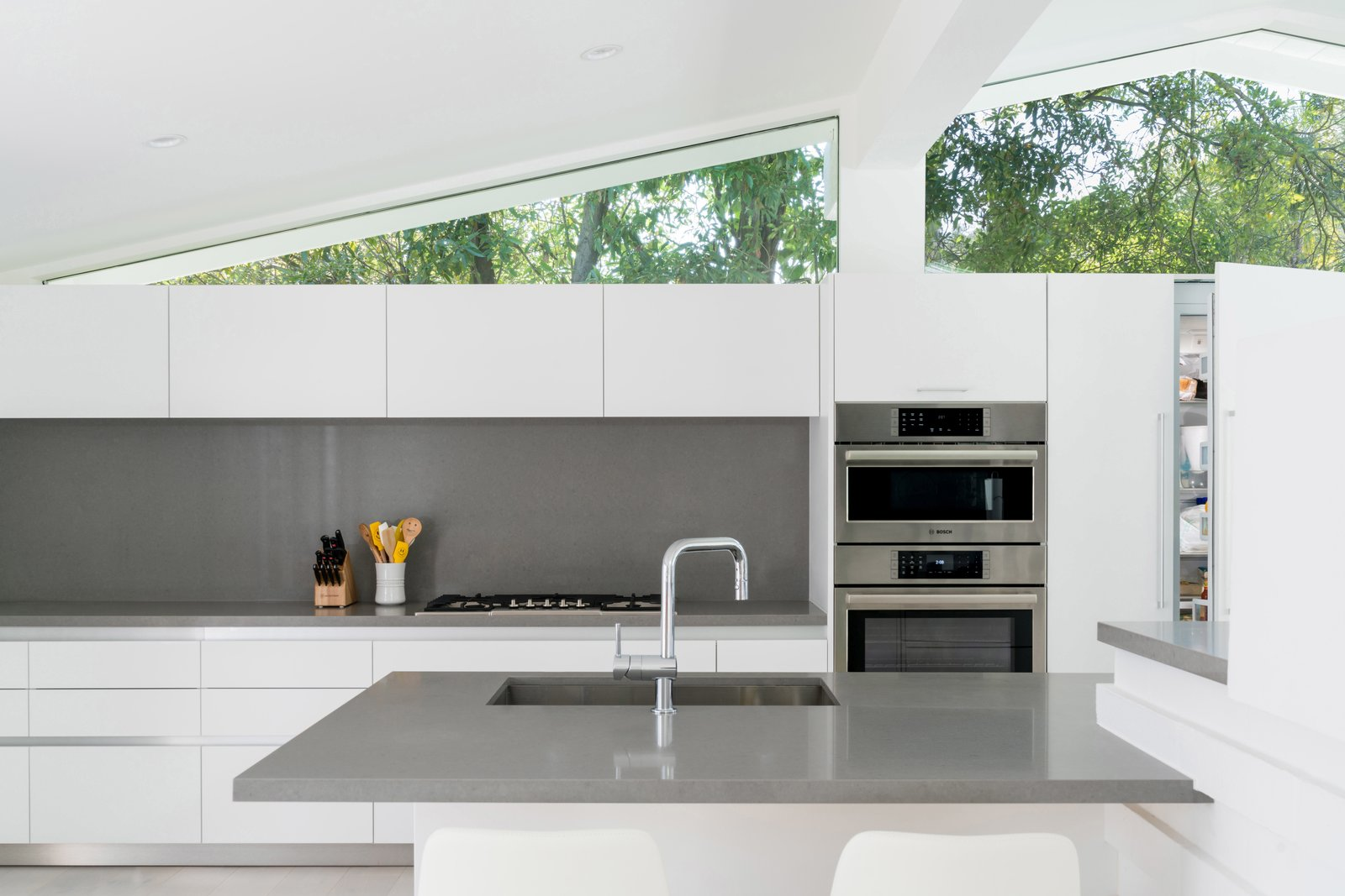 Kitchen, Engineered Quartz Counter, White Cabinet, Recessed Lighting, Wall Oven, and Undermount Sink The sleek oven duo, aligned beautifully with clerestories above, sits flush with kitchen cabinetry.  Photo 3 of 3 in A Breezy Midcentury Renovation in the Hollywood Hills