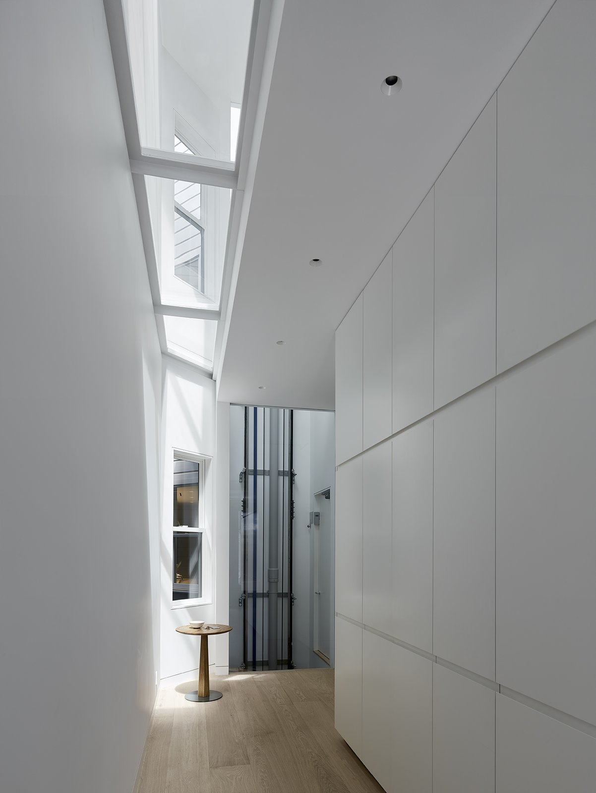 After: Alamo Square Residence indoor hallway with light hardwood flooring, white square panel details on the wall, and light from recessed lighting and skylights.