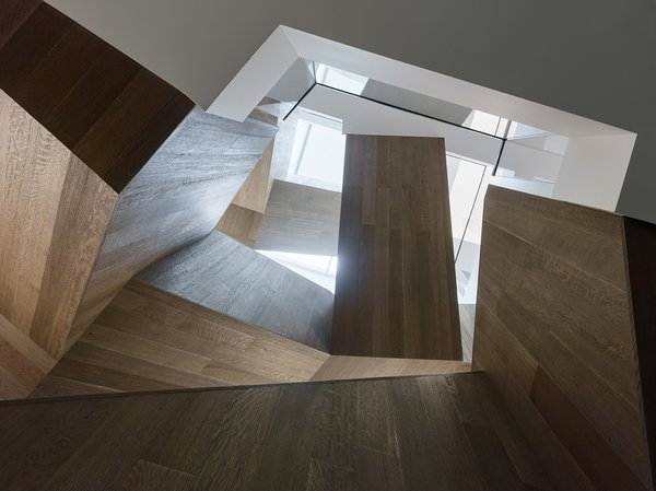The stair's folded volumes juxtapose solid wood forms with light-filled voids.