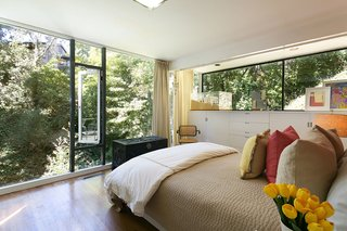 A corner bedroom's floor-to-ceiling windows allow sunlight to stream in, while the mature trees help maintain privacy.