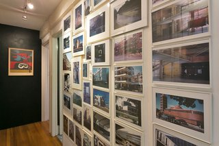An architectural photo collection adorns an entry wall.