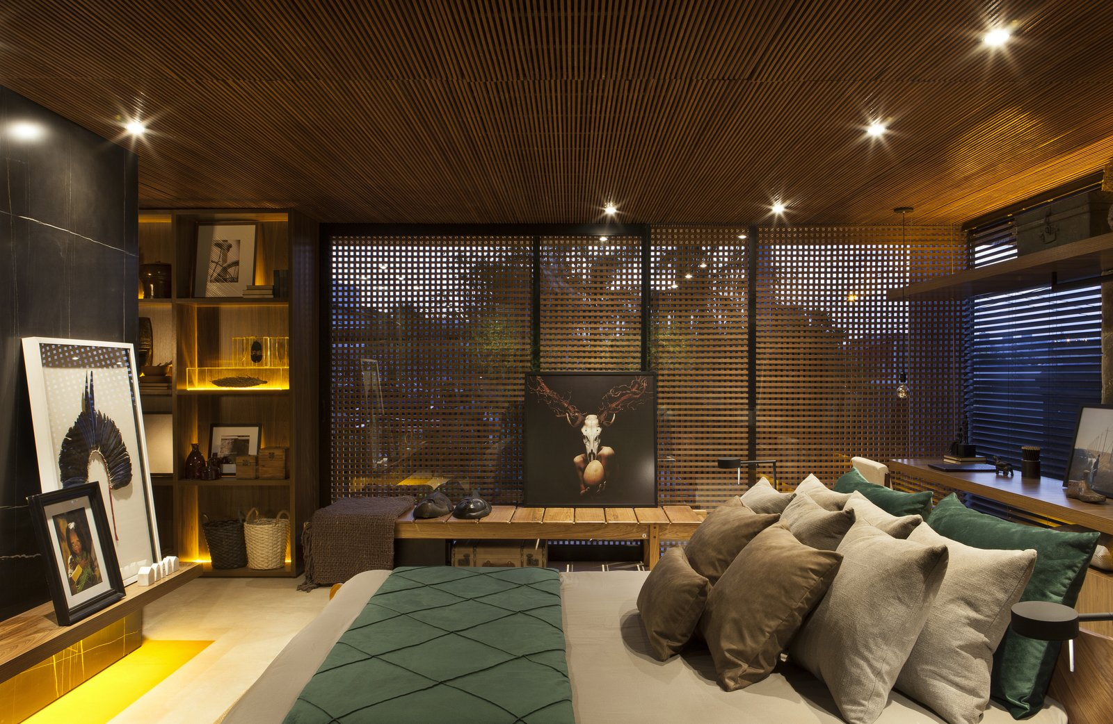 Bedroom, Bed, Ceiling Lighting, Recessed Lighting, Bench, Storage, and Shelves Seamlessly connected to the living room with no doors or dividers, the moody and luxe master bedroom is punctuated by collected art.  Photo 8 of 14 in An Incredible Brazilian Home That Celebrates Art, Travel, and Nature