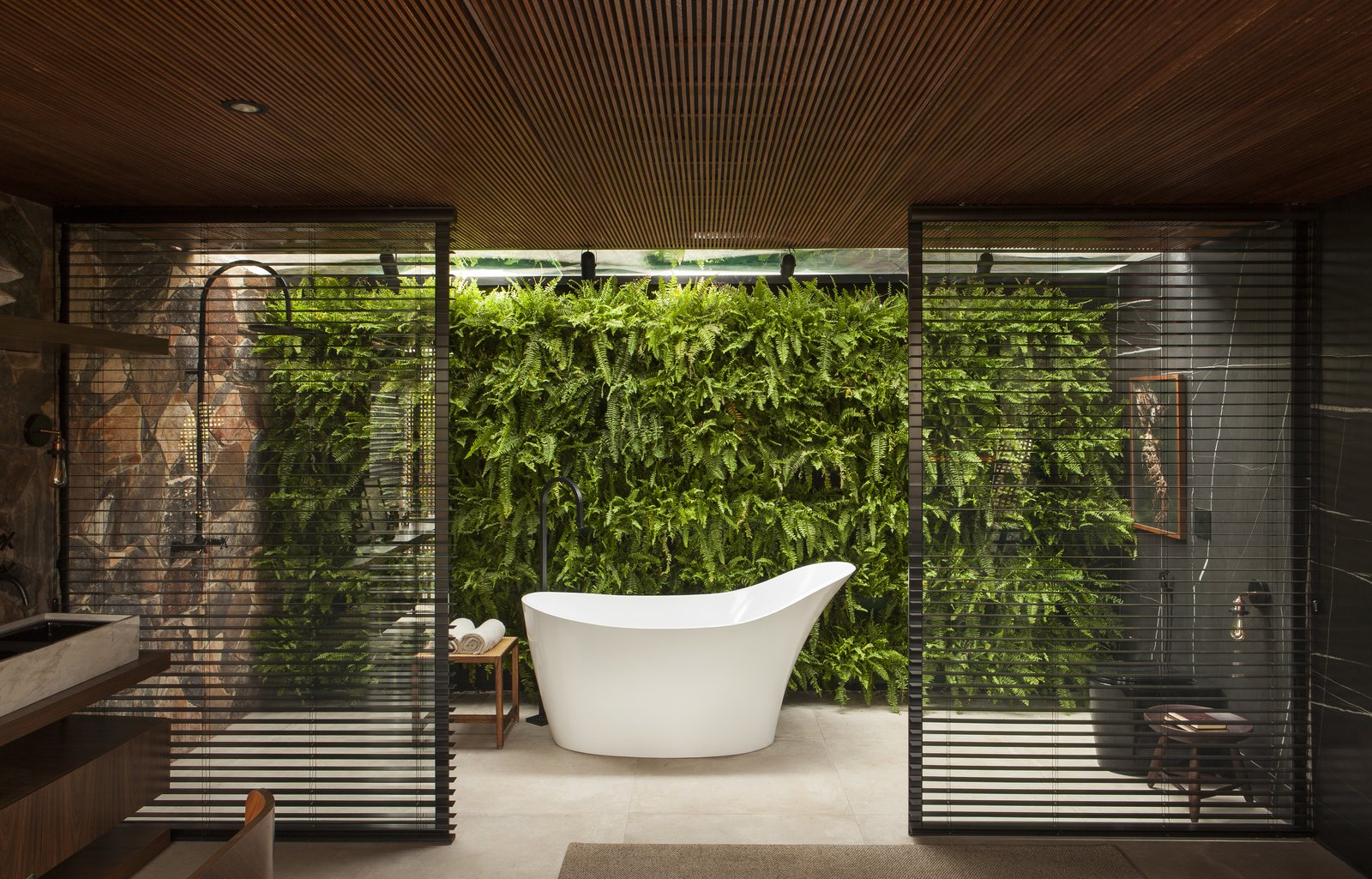 Bath Room and Freestanding Tub In the adjoining master bathroom, the soaking tub becomes a stunning focal point against the vibrant living backdrop.  Photo 10 of 14 in An Incredible Brazilian Home That Celebrates Art, Travel, and Nature