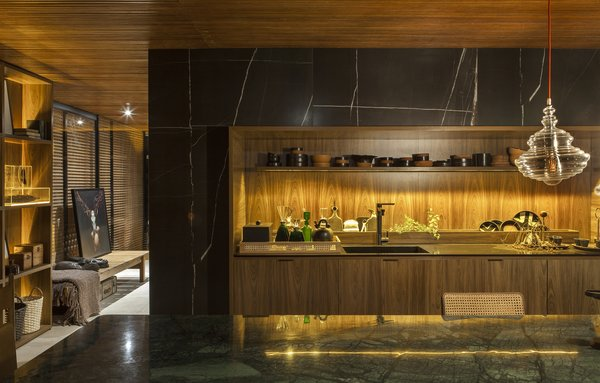 The home's kitchen marries a wood-slatted ceiling and wood cabinets with marble counter and surround.