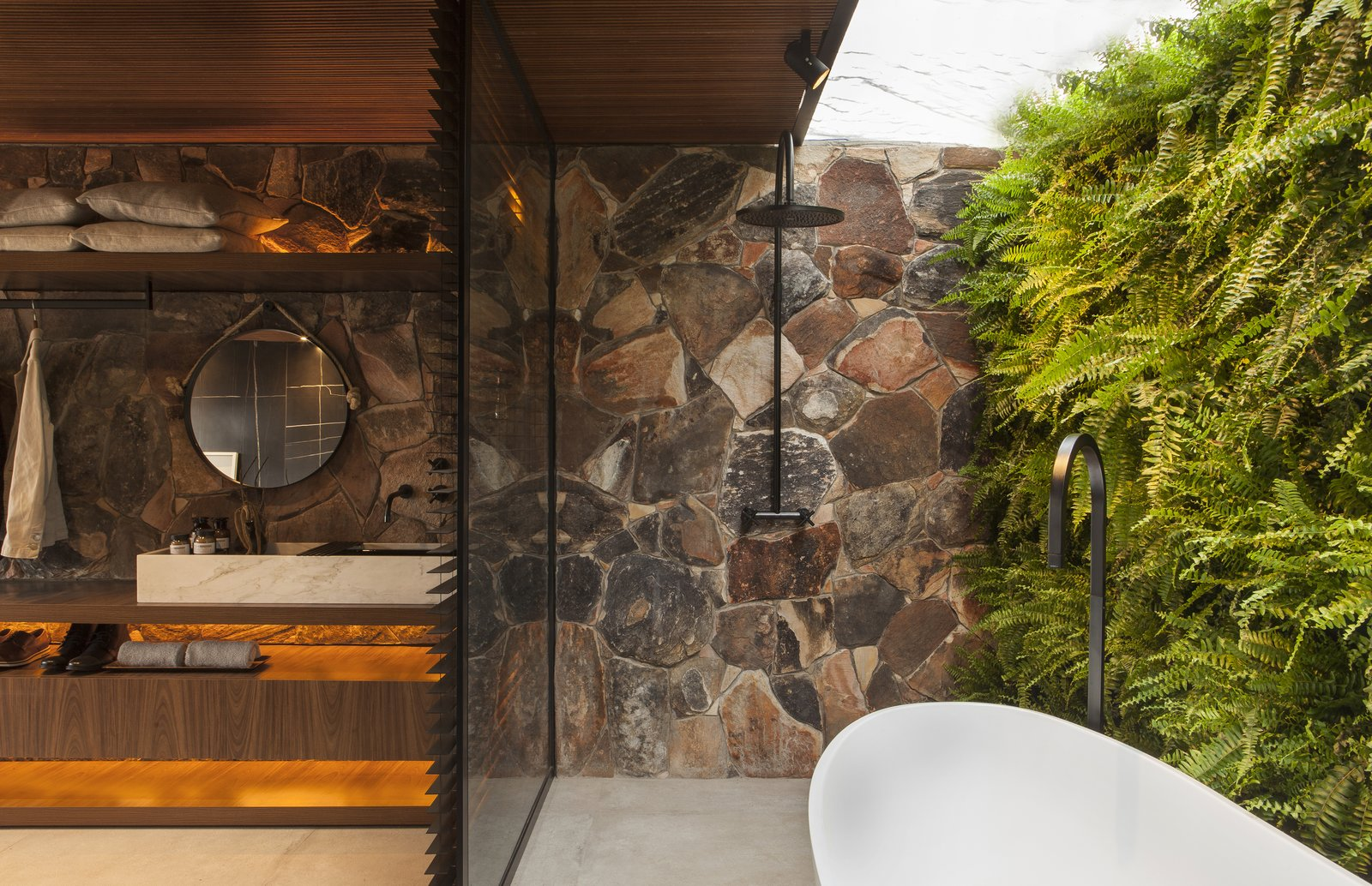 Bath Room, Freestanding Tub, Track Lighting, Vessel Sink, Concrete Floor, Wood Counter, and Stone Slab Wall Partially outdoors, the unconventional bathroom is a lush sanctuary.  Photo 11 of 14 in An Incredible Brazilian Home That Celebrates Art, Travel, and Nature