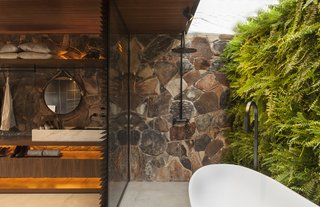 Partially outdoors, the unconventional bathroom is a lush sanctuary.