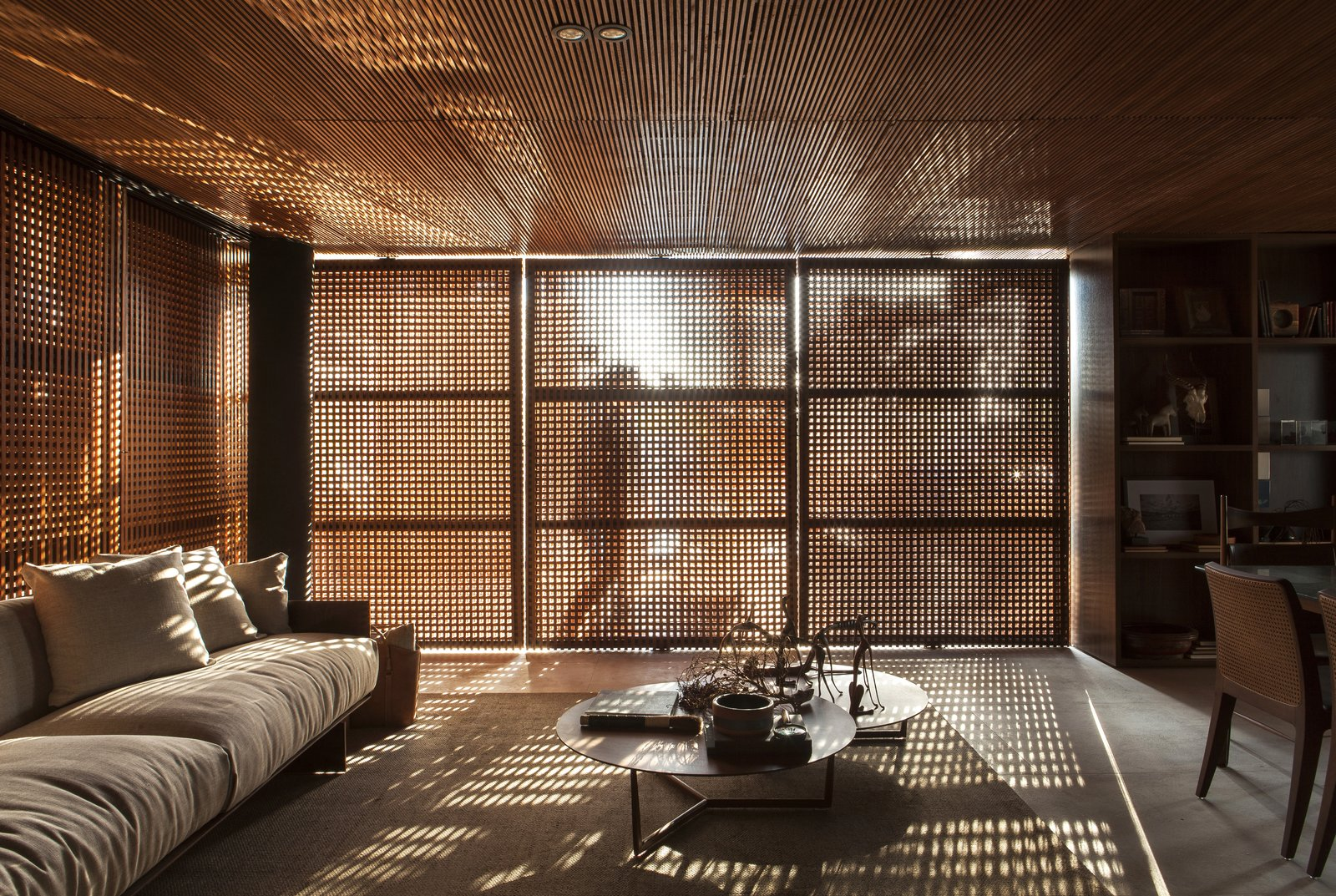Doors, Exterior, Wood, and Swing Door Type The slatted wood exterior selectively filters sunlight, cooling the interior and creating interesting light and shadow patterns.  Photo 7 of 14 in An Incredible Brazilian Home That Celebrates Art, Travel, and Nature