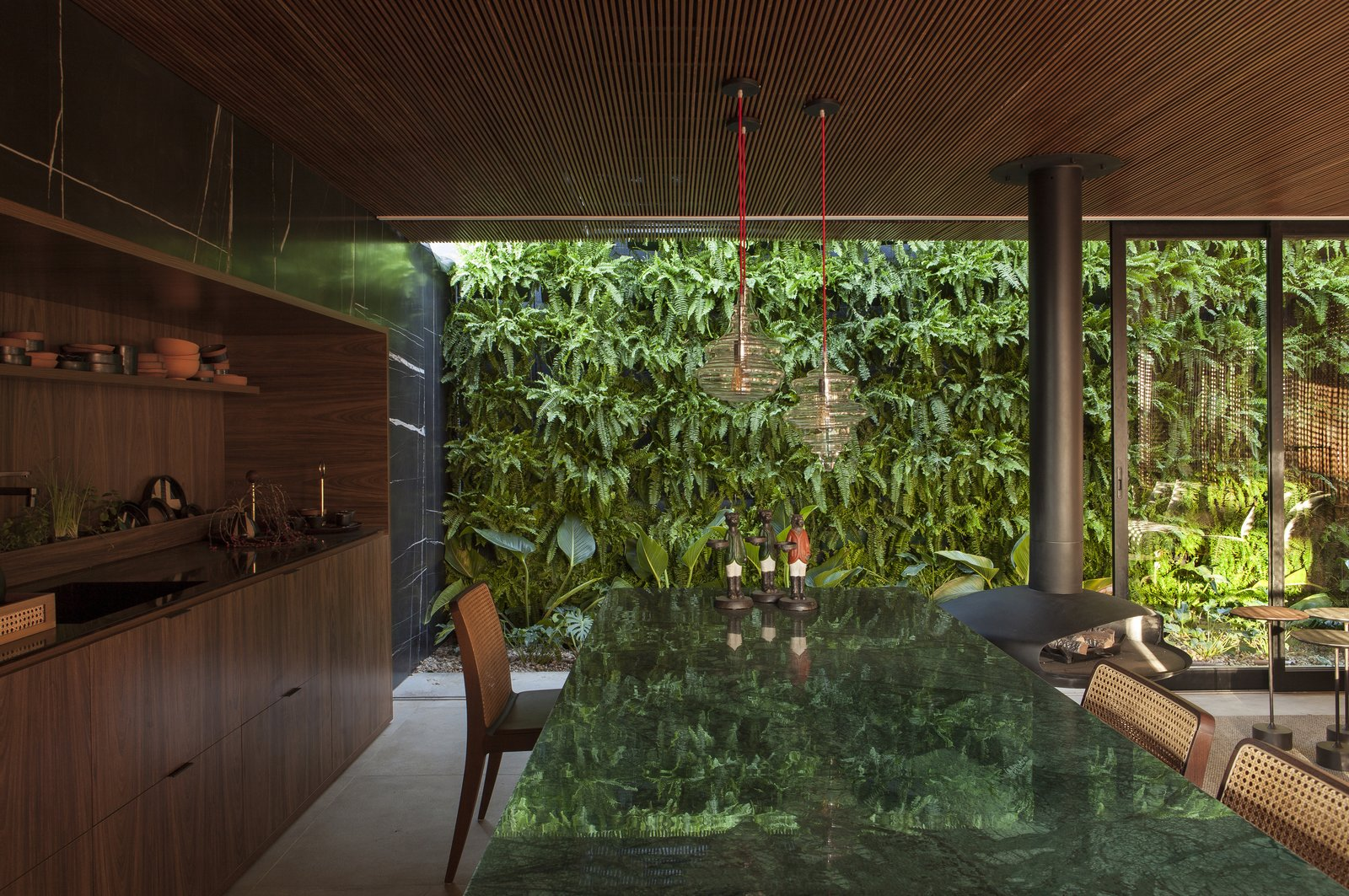 Dining Room, Table, Chair, Pendant Lighting, and Hanging Fireplace Sliding glass walls pocket into the exterior of the home, allowing the living space to be completely open to the lush vertical garden outside.  Photo 5 of 14 in An Incredible Brazilian Home That Celebrates Art, Travel, and Nature