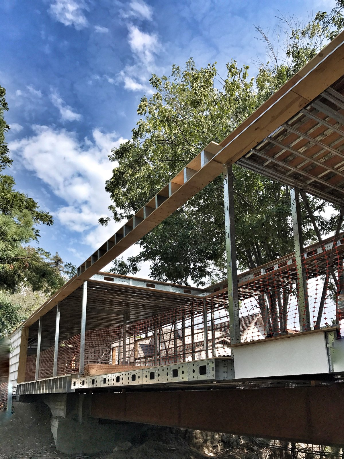 Exterior, House Building Type, and Flat RoofLine All on one level, Bridge House spans 210 feet across a stream in Hancock Park, Los Angeles. The structural undertaking was made possible by steel framework fabricated by BONE Structure.  Photo 2 of 7 in Dan Brunn Architecture and Dwell Break Ground on Bridge House in L.A.