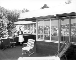 A 1950s photograph shows the upper-level terrace, remarkably consistent with architectural elements seen today.