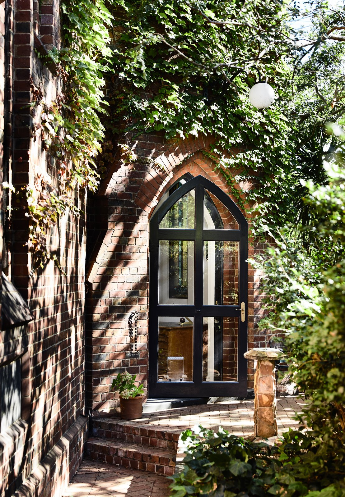 """Doors, Exterior, Swing Door Type, and Metal The embraced original character details of the church, including the arched glass doorway to the tower. When homeowner Jennifer and Grant initially viewed the space, the tower """"was just the icing on the cake.  Photos from Before & After: A 1930s Church in Melbourne Gets a Dramatic Conversion"""