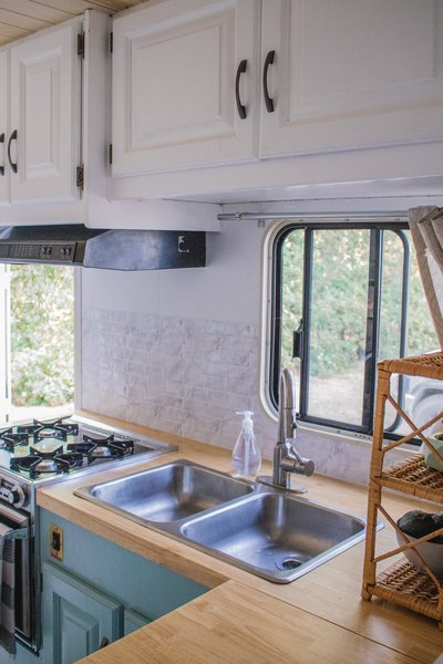 """Once the old countertops were pulled out, the couple used them as a template to cut the new ones. The tile backsplash (from Home Depot) uses stick-on tile. """"Real ones [tiles] have a propensity to fall off when the van hits bumps,"""" explains Grace."""