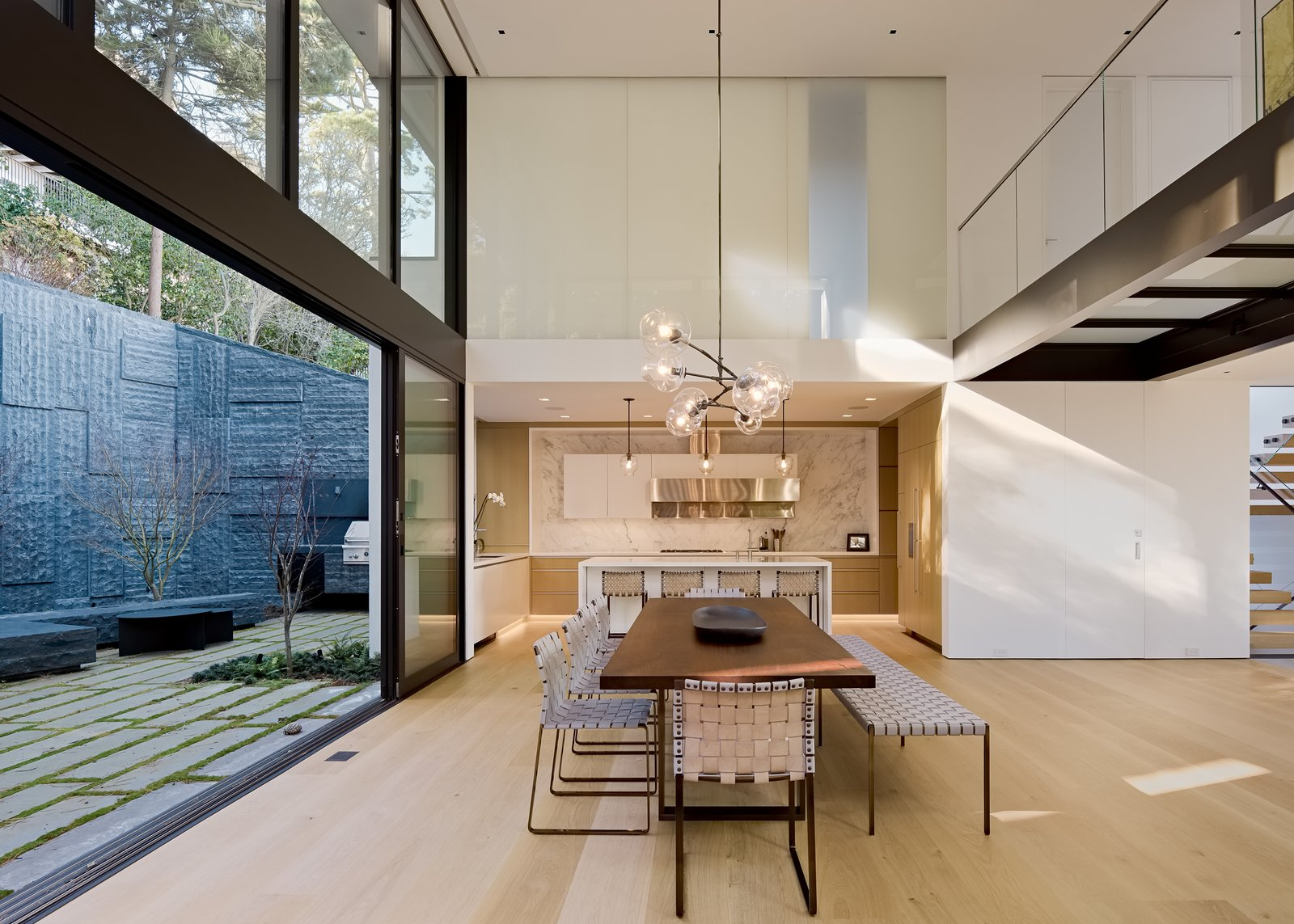 "Dining, Bench, Chair, Table, Pendant, and Light Hardwood Above the kitchen and dining room, a glass bridge connects bedrooms on the third floor. ""The glass flooring allows the southern light to penetrate farther into the space, but also creates a special moment of pause to experience the scale and volume of the space below and towering trees beyond,"" says Maniscalco.    Best Dining Light Hardwood Chair Bench Table Pendant Photos from A Steep, Sloping Lot Becomes a Hillside Family Oasis in San Francisco"