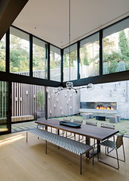 """Dining, Ribbon, Table, Chair, Pendant, Bench, Light Hardwood, Corner, and Gas Burning The double-height, fully glazed volume at the home's rear """"brings significant light into the home, while simultaneously creating a moment to experience the verticality of the surrounding trees which loom above the home,"""" explains Maniscalco.    Best Dining Light Hardwood Chair Bench Photos from A Steep, Sloping Lot Becomes a Hillside Family Oasis in San Francisco"""