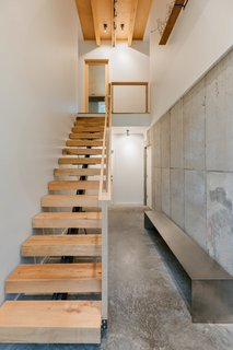 The interior stair is composed of floating treads sourced from trees cut down on the  property. A mix of oak, maple, and birch, each step is different and unique.