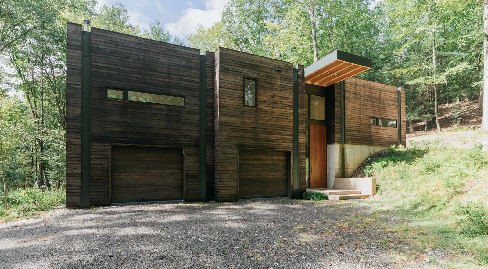 """Exterior, House Building Type, Wood Siding Material, and Flat RoofLine Positioned on a sloping hillside, the home is built into the land. The lower level is reserved for Marica and Brock's """"play"""" space, a workshop and garage, while the upper level houses the bright and airy living quarters.  Photo 2 of 12 in A Couple's Scenic Getaway Built For Creating and Tinkering  in New York's Hudson Valley"""