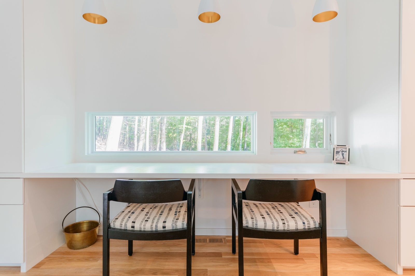 """Office, Chair, Desk, and Light Hardwood Floor The """"desk window"""" features small, horizontal openings which frame curated views of the trees beyond. Marvin Direct Glaze windows, and Ultimate Clad Casements make the quiet, reflective vantage point possible.  Photo 5 of 12 in A Couple's Scenic Getaway Built For Creating and Tinkering  in New York's Hudson Valley"""