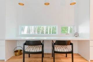 """The """"desk window"""" features small, horizontal openings which frame curated views of the trees beyond. Marvin Direct Glaze windows, and Ultimate Clad Casements make the quiet, reflective vantage point possible."""