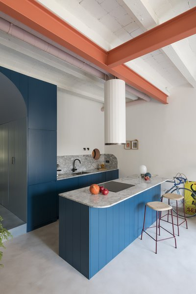 Hues of blue and coral create bold pops of color throughout the apartment. Painted coral I-beams follow the lines of what used to be partitions in the single, open space.