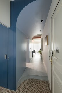 In the corridor between the living room and the bedrooms, light blue hues signal a transition from daytime to nighttime spaces. Serboli preserved the original geometric tile where possible, as in this area of the hallway off the private sleeping quarters.