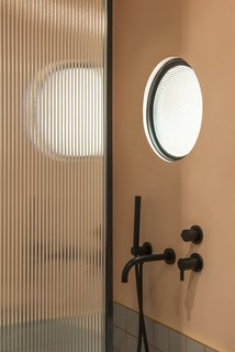 Optical glass, framed in matte black, features in both the shower screen and the circular portal window which adjoins the kitchen. It's a quirky touch that allows light to flow into the interior bathroom space.