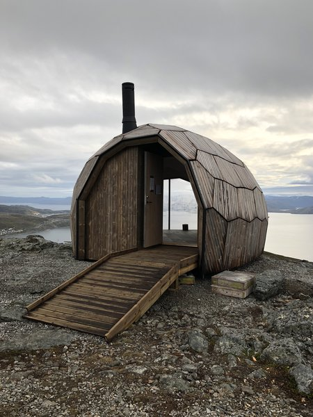 Hexagonal and pentagonal panels come together to form this cabin's oblong envelope. The unique architectural skin mimics the rock formations that surround it.