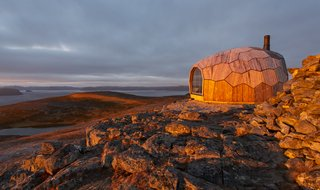 The small cabin's cross-laminated timber (CLT) shell, composed of 72 unique wooden panels, is designed to withstand severe arctic storms and heavy wind conditions.