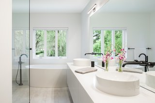 The master bathroom features an American Standard soaking tub with a Brizo tub filler, along with Kohler vessel sinks and Brizo faucets.