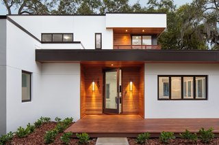The cedar-clad recessed entryway of Hyde Park House, with a generous front deck, warmly welcomes visitors.