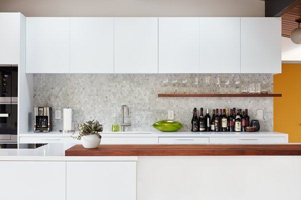 A custom walnut slab bar counter and shelf, along with a hex tile backsplash, add pops of texture and depth to an otherwise clean and monochrome palette.