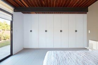 A wall-to-wall custom wardrobe offers smart storage.