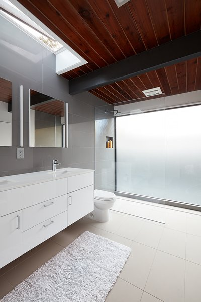 The home's bathrooms feature Lacava undermount sinks, Hansgrohe fixtures, and Duravit toilets. Natural light filters in through a skylight above the vanity.