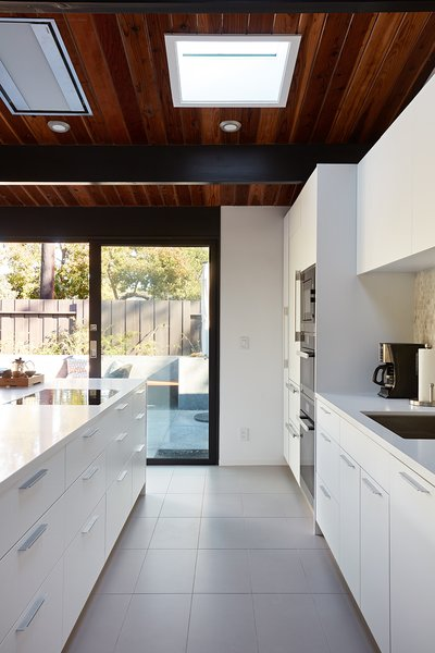 The bright and airy kitchen is flooded with light from all directions. The inviting space enjoys visual connections to both the side patio and rear yard.