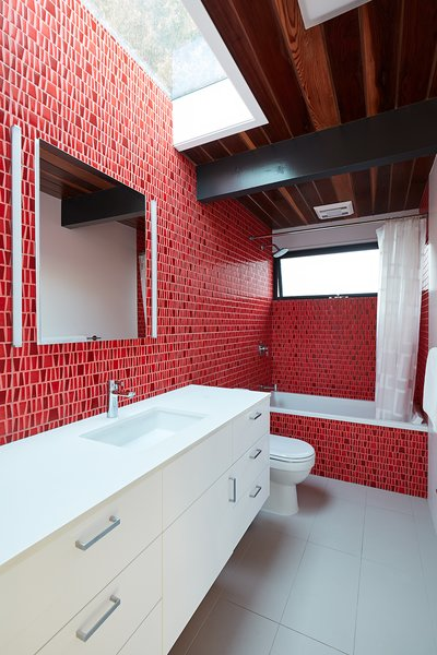 Client-selected Porcelanosa mosaic tile adds a pop of color to the guest bathroom.