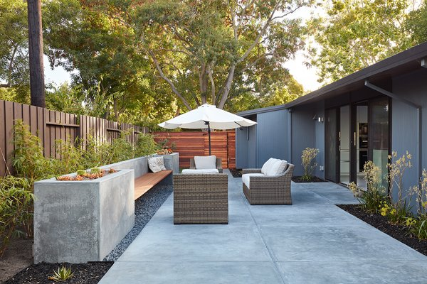 The side patio, adjacent to the kitchen, offers additional outdoor living space with casual seating and an integrated concrete bench.