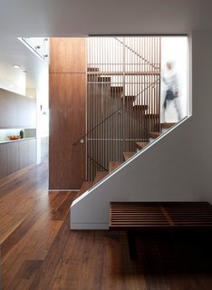 A slatted walnut screen is a centerpiece of the home's new design. Accentuating the height of the space, the vertical slats come together with metal rods and a sleek handrail, creating a graphic manipulation of positive and negative space. In addition to allowing light to permeate the interior, the screen is visible from most vantage points in the home, providing an anchor of visual interest.