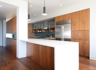 """""""We knew we wanted enough room for a family—and we wanted to emphasize cooking, and have more of a communal space,"""" says homeowner Jeff of their renovation priorities. The centrally located kitchen features walnut cabinetry, Caesarstone countertops in Pure White, a Heath tile backsplash, and Pablo Designs Cielo pendants. Appliances include a SubZero French-door refrigerator, BlueStar range, and Zephyr vent hood."""