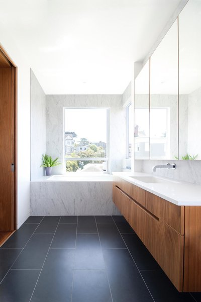 The new master bathroom features a large soaking tub clad in Carrera marble tile from Daltile. A new Milgard window highlights southern city views.